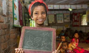 A child with disability, happily holds the slate to display her drawing skills during a class at the UNICEF-supported BRAC pre-primary school in Soyghoria village, Bangladesh.