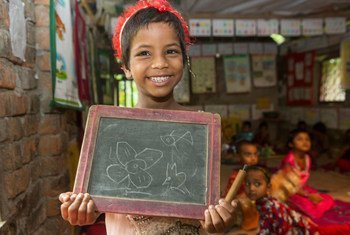 Una niña con una discapacidad sujeta una pizarra para mostrar su dibujo en un centro de educación prescolar apoyado por UNICEF en Bangladesh.