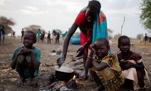 A woman cooks a meal outside in the open air with her three children where she is camping with her family the night before being able to register for a ration card  in Thanyang, South Sudan.