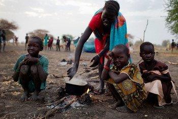 Une femme prépare un repas avec ses trois enfants à Thanyang, au Soudan du Sud. Photo UNICEF/Kate Holt