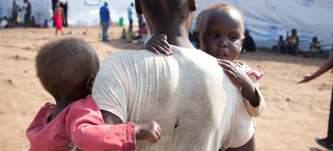 Halima, a South Sudanese refugee carries two of her children in Bidi Bidi refugee settlement in northern Uganda. Having lost her husband in the conflict in South Sudan, she must endure this alone, and depend on the UN WFP for food and nutrition.
