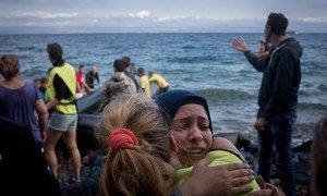 Refugees, primarily from Syria, Iraq and Afghanistan are helped by volunteers as they disembark boats near Scala, on the island of Lesvos, Greece.