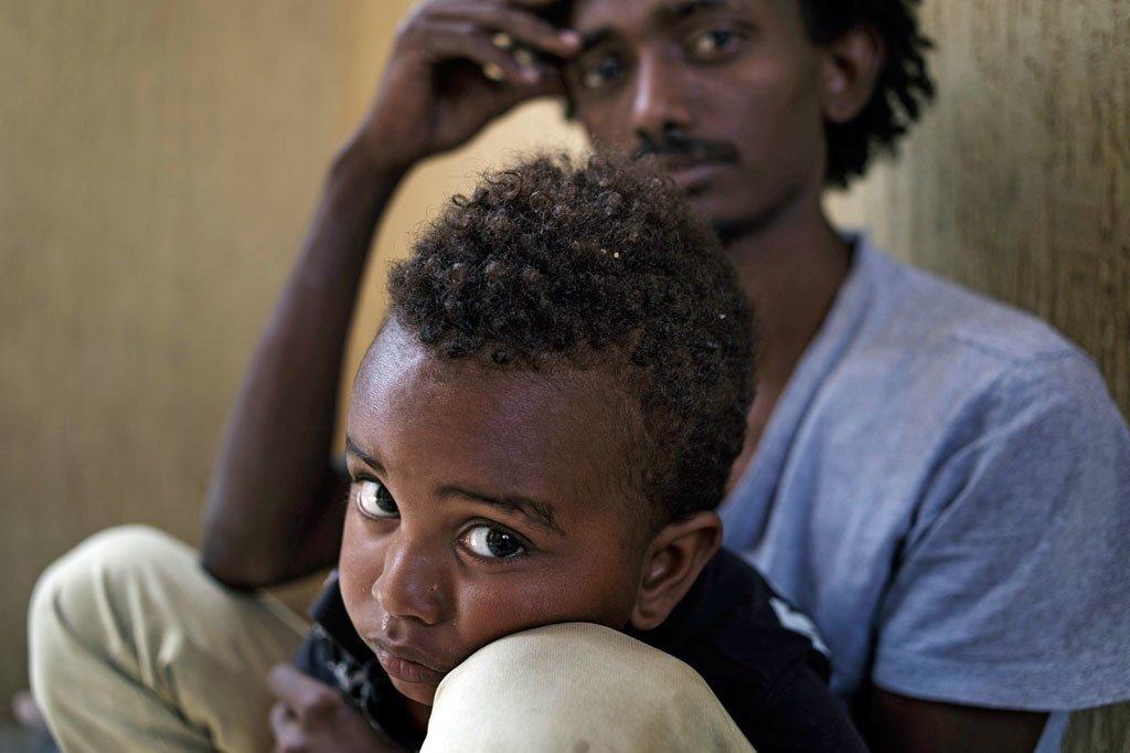 En Libye, Addis, tient dans ses bras son fils, Lato, dans un centre de détention de la ville de Garabulli.