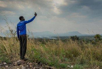 Беженец из Южного Судана в Уганде пытается поймать сигнал для своего мобильного телефона.