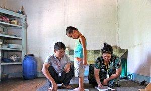 Des professionnels de santé mesurent et enregistrent la taille et le poids d'Erlan Bernoupereinev, 3 ans, chez lui, dans le village de Kindik Uzyak, en Ouzbékistan. Photo UNICEF/Giacomo Pirozzi