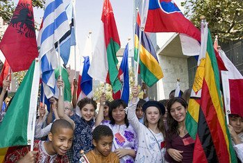 Cheerful young students in their traditional dress proudly waive their national flags during the Peace Bell ceremony of the observance of the International Day of Peace at UN Headquarters in New York.