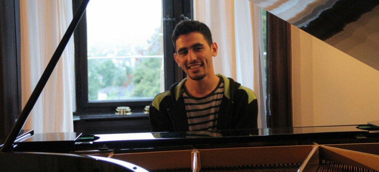 Ayham al-Ahmad sits behind his piano.
