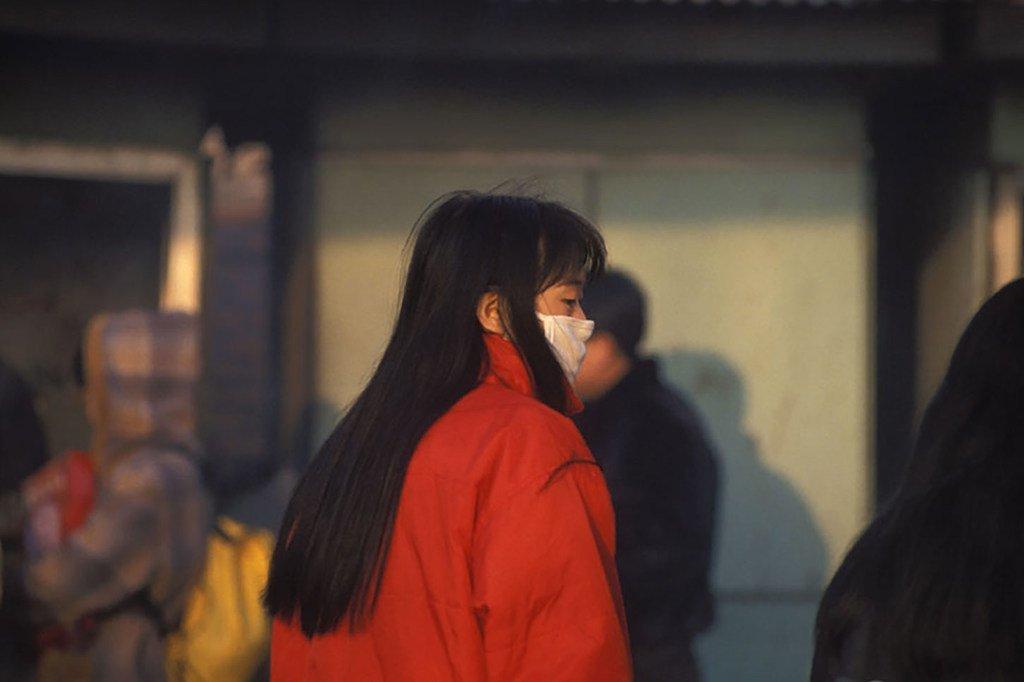 امرأة ترتدي قناعا للحماية من التلوث. الصين.