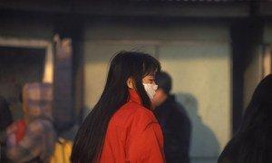 Una mujer en China utiliza un tapabocas.