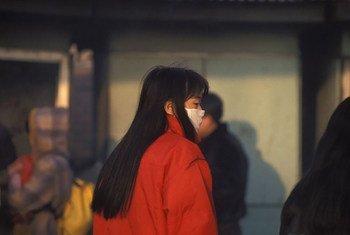 Une femme portant un masque pour se protéger de la pollution en Chine. Photo Banque mondiale/Curt Carnemark