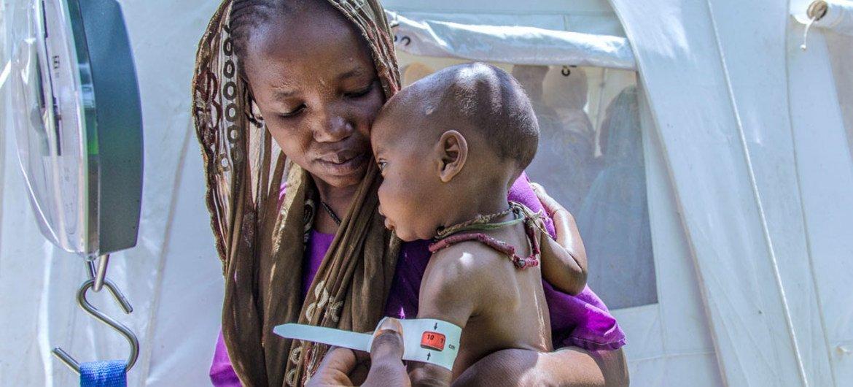 Una madre desplazada lleva a su hijo a uno de los centros de UNICEF en Borno, Nigeria, para que lo traten por desnutrición aguda grave. Foto: UNICEF/Andrew Esiebo