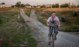 Un homme circule à vélo dans le village de Novosvetlovka, dans l'est de l'Ukraine (archives). Photo HCR/Petr Shelomovskiy