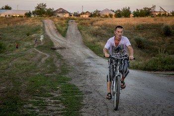 Сельский житель   едет  на велосипеде в свою деревню  Новосветловка на востоке Украины . Фото УВКБ