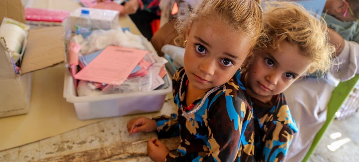Two girls wait in line at a temporary medical centre in Bzebiz Displacement Camp in Baghdad, Iraq.