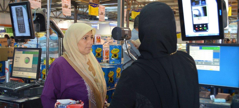 Hana Heraaki, a Syrian refugee in Zaatari camp, looks into the iris scan camera.