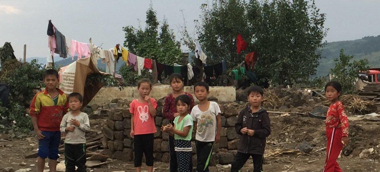Hoeryong, RPDC : des enfants observent la mission d'évaluation inter-agences de l'ONU évaluer les besoins des personnes touchées par les inondations en 2016. En 2018, 111 millions de dollars sont nécessaires pour financer l'aide humanitaire en RPDC.