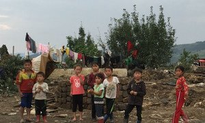 Children in Hoeryong City, Democratic People's Republic of Korea (DPRK), observe a UN inter-agency assessment mission that evaluated the needs of people affected by floods in September 2016.
