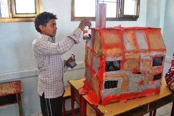 طفل يمني نازح يصمم منزلا مشابها لمنزله المدمر في صنعاء، كجزء من برنامج علاج صحته النفسية.