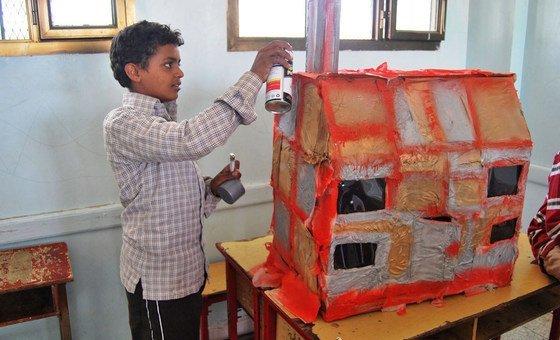 也门萨达一名流离失所的男孩在为他被毁的房屋制作复制品,作为他心里健康治疗的一部分。