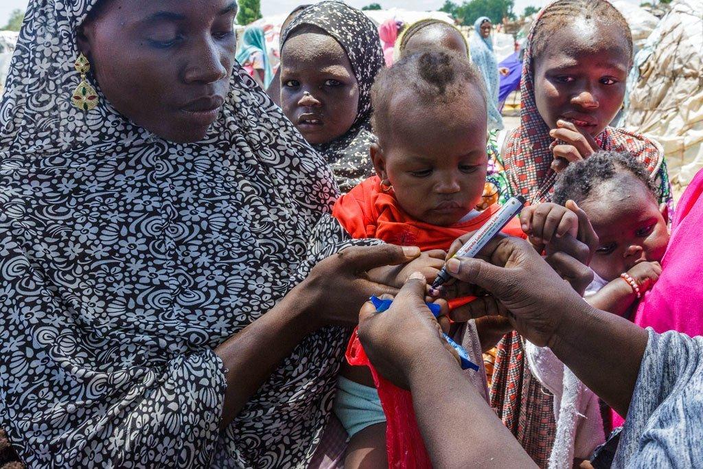 عاملة صحية في اليونيسف تستخدم قلماً لوضع علامة على إبهام أجيدا مالام البالغة من العمر 6 أشهر، التي تم تطعيمها للتو ضد شلل الأطفال في مخيم للنازحين خارج مايدوغوري شمال شرق نيجيريا.