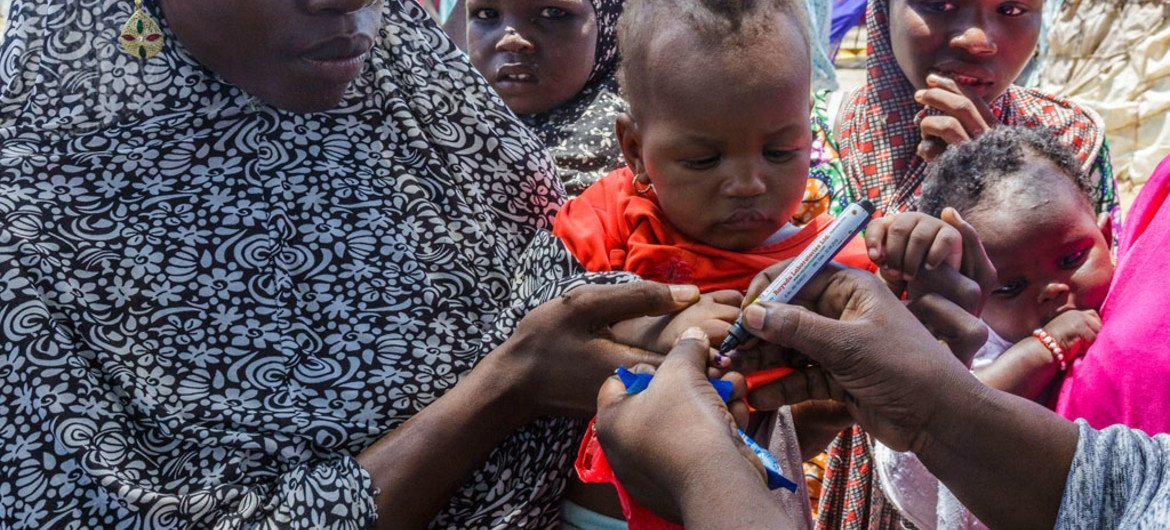 UNICEF health worker uses a pen to mark the thumb of Ajeda Mallam, 6 months, who has just been vaccinated against polio at a camp for internally displaced persons outside Maiduguri northeast Nigeria. Photo: UNICEF/Andrew Esiebo