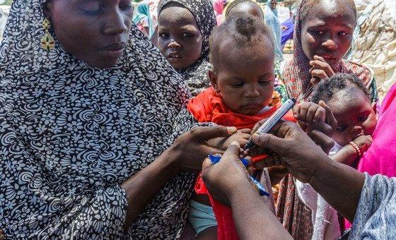 Profissional de saúde do Unicef usa uma caneta para marcar o polegar de Ajeda Mallam, de 6 meses, que acaba de ser vacinado contra a poliomielite em um campo para pessoas deslocadas internamente, no nordeste da Nigéria.