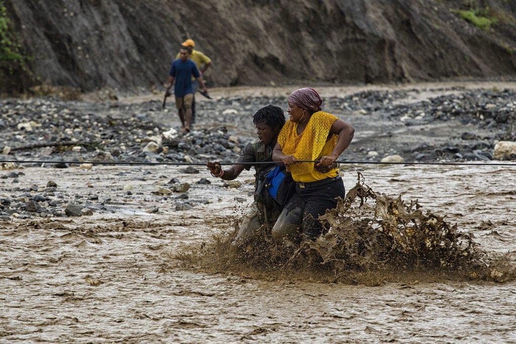 Watu wakiwa katika mto uliofurika Magharibi mwa Haiti baada ya daraja kusombwa na maji kufuatia kimbunga Matthew