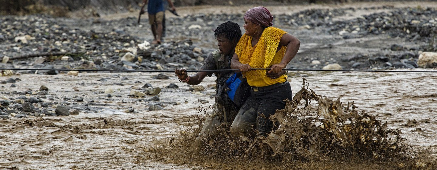 People cross a flooded river in western Haiti after a bridge was washed away by Hurricane Matthew. (file)