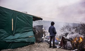 A young resident at the so-called Calais 'jungle' views the harsh winter landscape of the temporary center, home at times to several thousand persons.