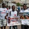लाइबेरिया में बलात्कार विरोधी पोस्टरों के साथ पुरुषों का मार्च