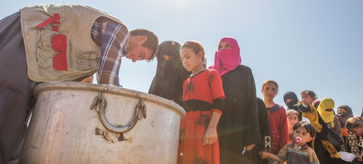 Iraqi women and children displaced from the Mosul corridor line up to recieve food in Debaga Displacement Camp in Erbil Governorate.