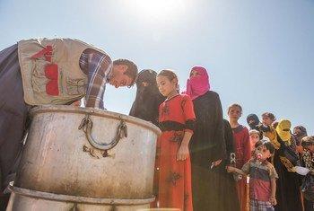 Des femmes et des enfants iraquiens déplacés de la région de Mossoul font la queue pour recevoir de la nourriture dans le camp de Debaga dans le gouvernorat d'Erbil. Photo UNICEF/Anmar