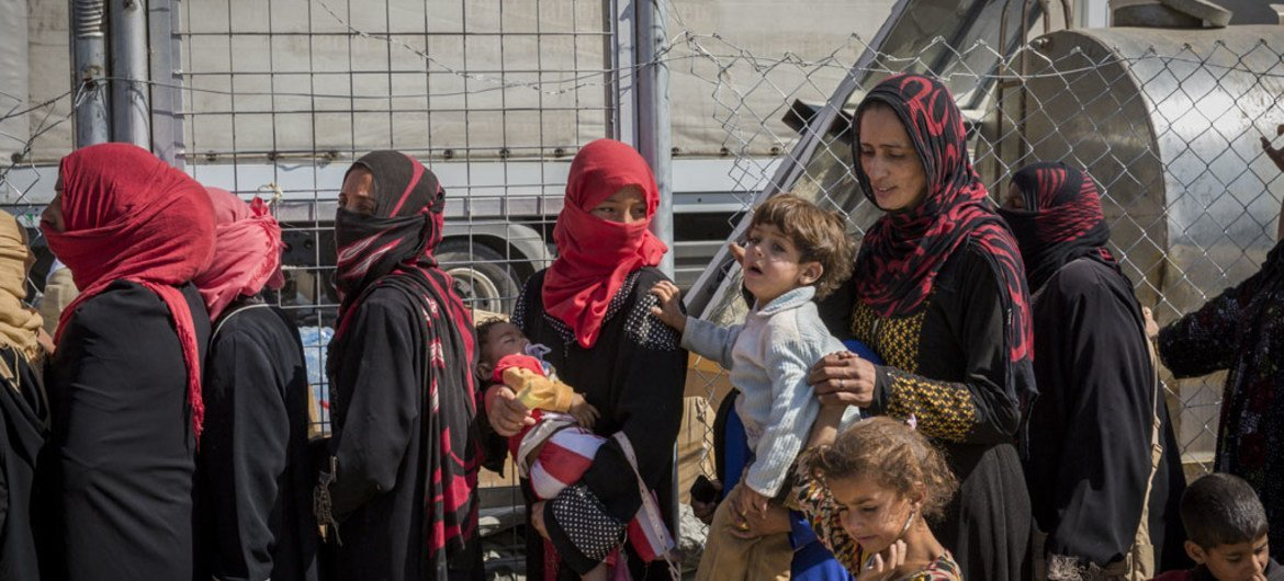 Displaced Iraqi women line up to receive food and water at Debaga camp for internally displaced people in Iraq's Erbil Governorate.