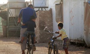 A father and his children in Jordan's Zaatari camp prepare to travel on their bicycles.