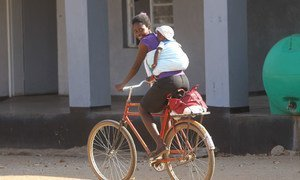 Une mère et son enfant à vélo, dans la province de Matebeland, au Zimbabwe.