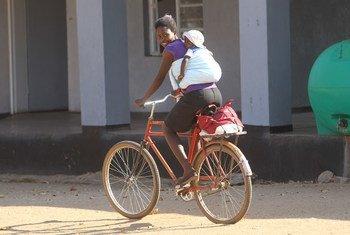 Mama mmoja aendesha baiskeli akiwa amebeba mtoto mgongoni katika mkoa wa kusini Matebele, Zimbabwe.