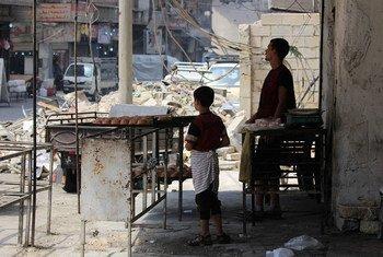 Un enfant et un homme font cuire de la nourriture à Alep, en Syrie. Photo UNICEF/Rami Zayat