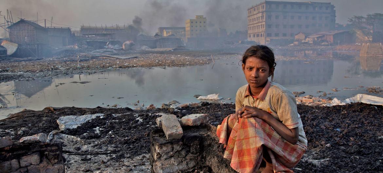 فتاة صغيرة تجلس على حطام مصنع للغراء حيث تعمل على جمع النفايات لصنع الغراء-بنغلاديش