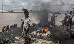 Des enfants à côté de déchets qui brûlent dans un abattoir à Yenagoa, au Nigéria.