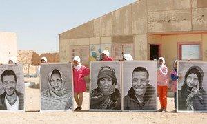 Des réfugiés du Sahara occidental avec des portraits à l'extérieur du camp de réfuiés de Smara, près de Tindouf, en Algérie. Photo ONU/Evan Schneider