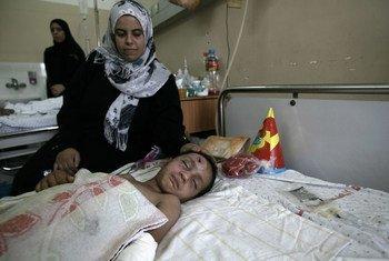 Familiar cuida de menino de três anos no Hospital Al-Shifa, ferido numa explosão que matou 12 membros da sua família.