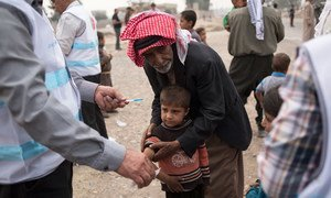 A boy who fled a village south of Mosul, Iraq, receives a measles vaccination from a UNICEF-supported government health worker at an aid distribution in Ibrahim Khalil.
