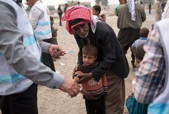 Un garçon qui a fuit un village au sud de Mossoul, en Iraq, est vacciné contre la rougeole par un fonctionnaire de la santé soutenu par l'UNICEF sur un site de distribution d'aide à Ibrahim Khalil.