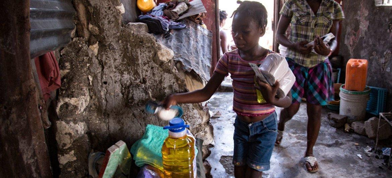 Una niña abre un paquete con productos de higiene distribuidos tras el paso del huracán Matthew en un área afectada por el cólera en Haití. Foto: UNICEF/Roger LeMoyne