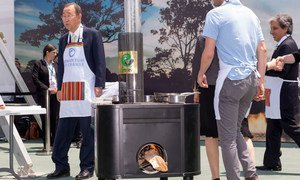 Secretary-General Ban Ki-moon (left) stands behind one of the fuel-efficient cook stoves used in the demonstration of sustainable cooking at the UN Climate Change Conference in Lima, Peru, in December 2014.