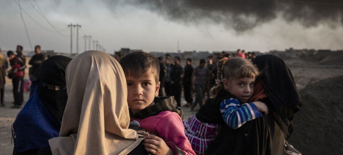 Families displaced by fighting in the village of Shora, 25 kilometres south of Mosul, gather at an army checkpoint on the outskirts of Qayyarah.