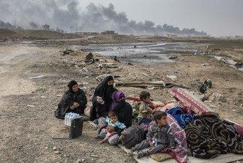 Une famille déplacée par les combats dans le village de Shora à 25 kilomètres au sud de Mossoul, attend au bord de la route près d'un point de contrôle militaire à l'extérieur de Qayyarah.