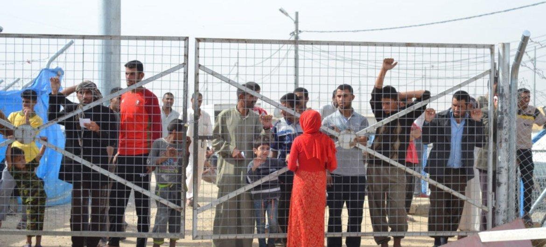 Des hommes sont détenus derrière le grillage du camp de Debaga. Ils reçoivent la visite de leurs femmes et enfants en attendant d'être que les forces de sécurité kurdes terminent leur enquête et les acquittent de tout lien avec l'EIIL.