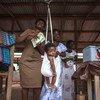 在加纳,一名社区卫生工作者在接种疫苗之前给一名婴儿称体重。 2012年,加纳成为非洲第一个同时引入肺炎球菌病和轮状病毒疫苗的国家,以应对世界上主要的两种致命儿童疾病:肺炎和腹泻。
