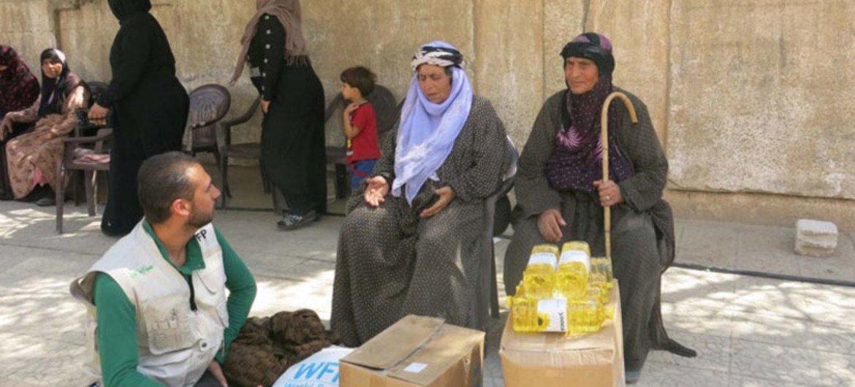 Des veuves à Qamishly, en Syrie, parlent avec un fonctionnaire du PAM dans un centre de distribution de nourritures.